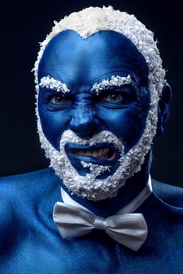 在与多雪的做鬼脸头发和的胡子的蓝色颜色绘的人 库存照片