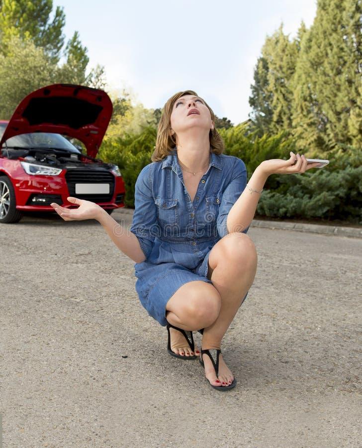 在与拜访手机的残破的发动机失败崩溃事故的路旁搁浅的可爱的绝望和迷茫的妇女 免版税库存照片