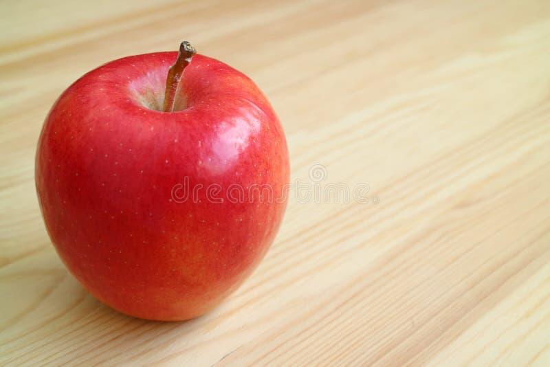 在与拷贝空间的浅褐色的木桌上隔绝的新鲜的成熟充满活力的红色苹果 库存图片