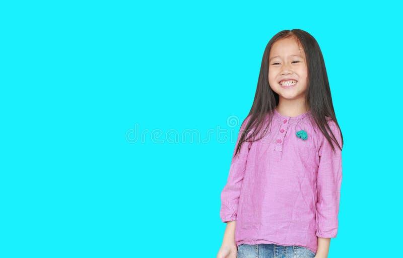 在与拷贝空间的深蓝背景隔绝的愉快的矮小的亚裔儿童女孩画象  孩子微笑的概念 免版税库存照片