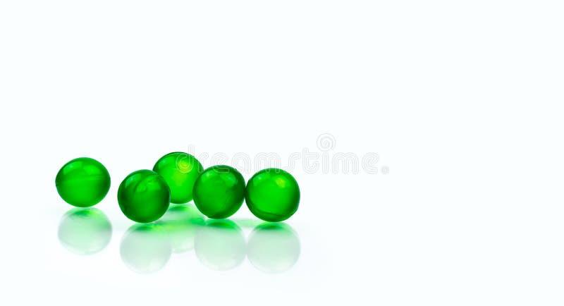 在与拷贝空间的白色背景隔绝的五个绿色圆的软的胶囊药片 消化不良的,气体Ayurvedic医学 免版税库存照片