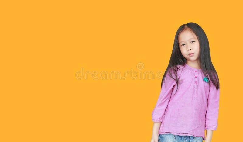 在与拷贝空间的黄色背景隔绝的微笑的小亚裔儿童女孩画象  孩子微笑的概念 库存照片