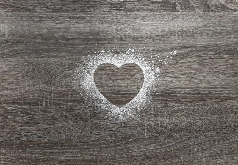 在与搽粉的粉末雪的木背景心脏的剪影 库存图片