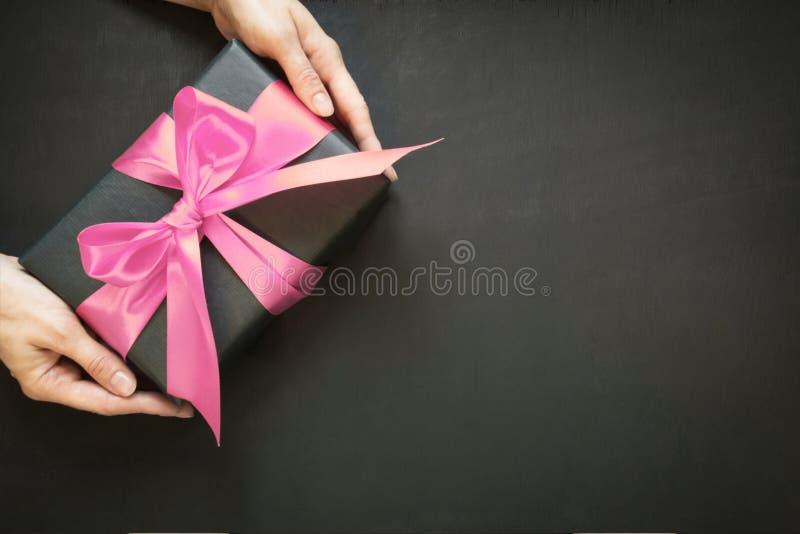 在与桃红色缎丝带的黑纸包裹的礼物盒在黑表面上的女性手上 复制空间 在视图之上 图库摄影