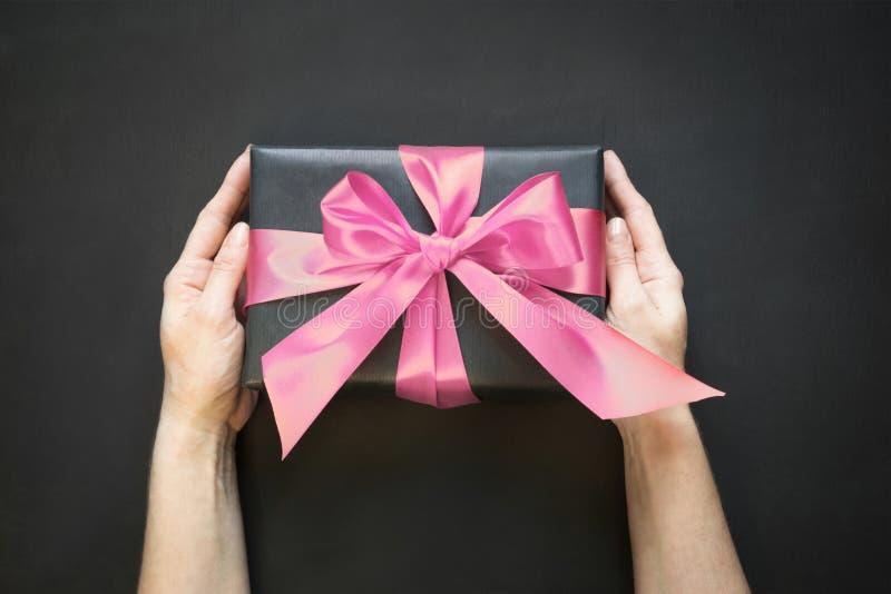 在与桃红色缎丝带的黑纸包裹的礼物盒在黑表面上的女性手上 复制空间 在视图之上 免版税图库摄影