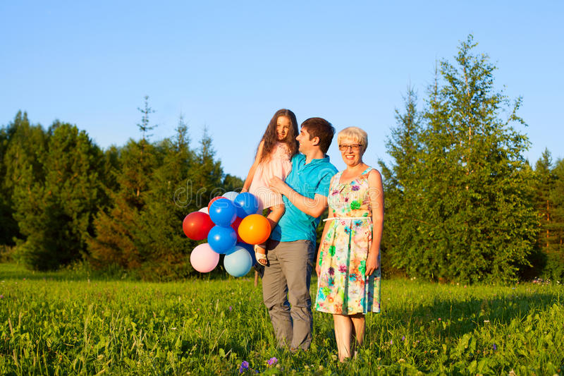 在与气球的日落期间美丽的愉快的家庭户外 免版税图库摄影