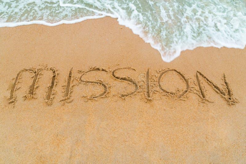 在与波浪接近的沙滩写的使命题字 免版税库存图片