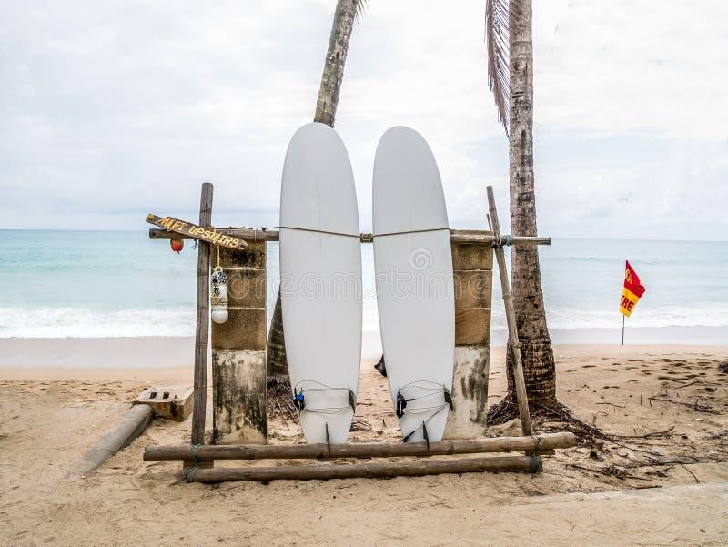 在与波浪的一个空的沙滩放弃的白色冲浪板在距离 库存图片