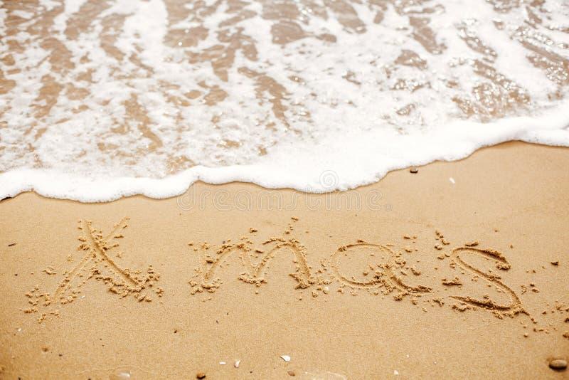 在与波浪的沙滩写的Xmas文本在海附近 旅行和 库存照片