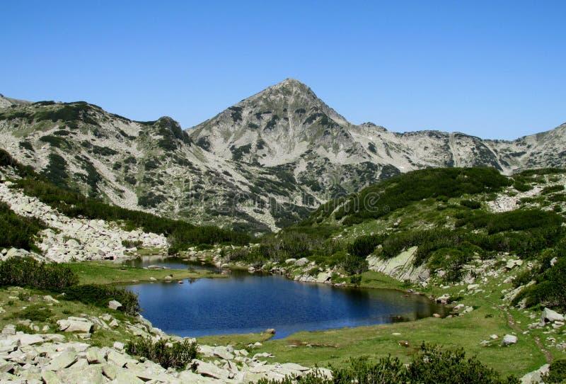 在与清楚的蓝天的晴天期间在保加利亚、深蓝色湖和灰色岩石山顶的Rila山 免版税库存图片