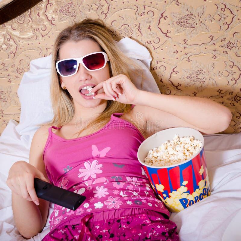 在与电视遥控手中观看的电影的床上在3D玻璃和吃玉米花的颜色睡衣的白肤金发的少妇 免版税库存照片