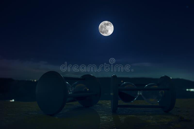 在与穿过测量通过的蒂姆的滴漏的玻壳的月亮或沙子的晚上计时与滴漏的概念 免版税图库摄影
