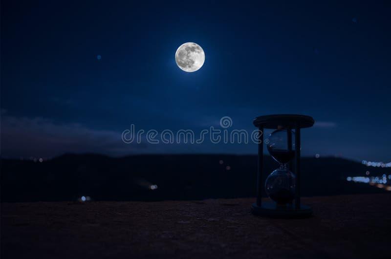 在与穿过测量通过的蒂姆的滴漏的玻壳的月亮或沙子的晚上计时与滴漏的概念 免版税库存图片