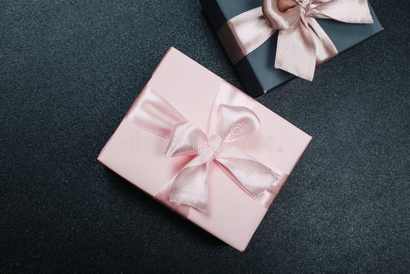 在与红色、金子和桃红色丝带的纸包裹的美丽的礼物盒黑表面上 r 免版税库存图片
