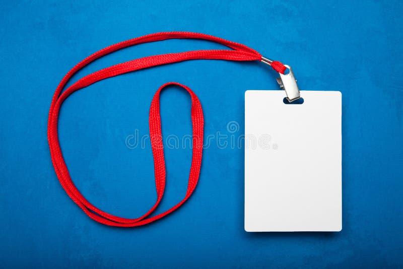 在与红色丝带的蓝色隔绝的空白的徽章大模型 库存照片