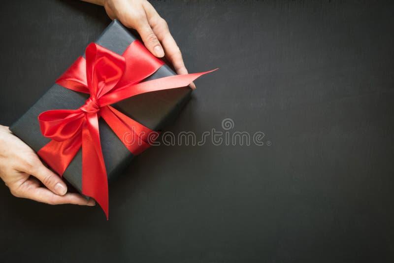 在与红色丝带的黑纸包裹的礼物盒在黑表面上的女性手上 免版税库存照片
