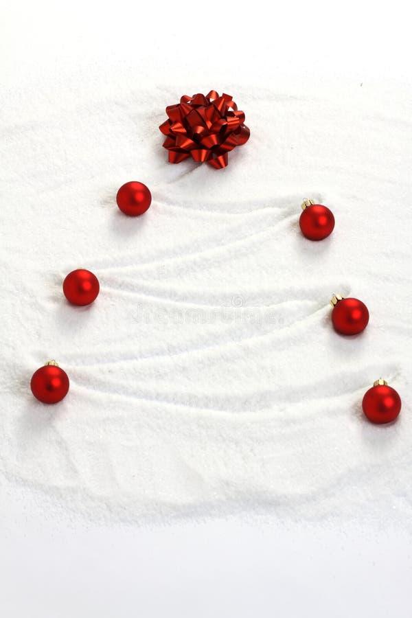 在与红色弓和红色暗淡圣诞节球的雪绘的圣诞树 库存照片