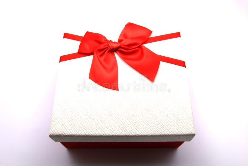 在与红色弓的白色背景礼物隔绝的礼物盒在与银色闪闪发光的白色土气背景 欢乐的背景 免版税库存照片