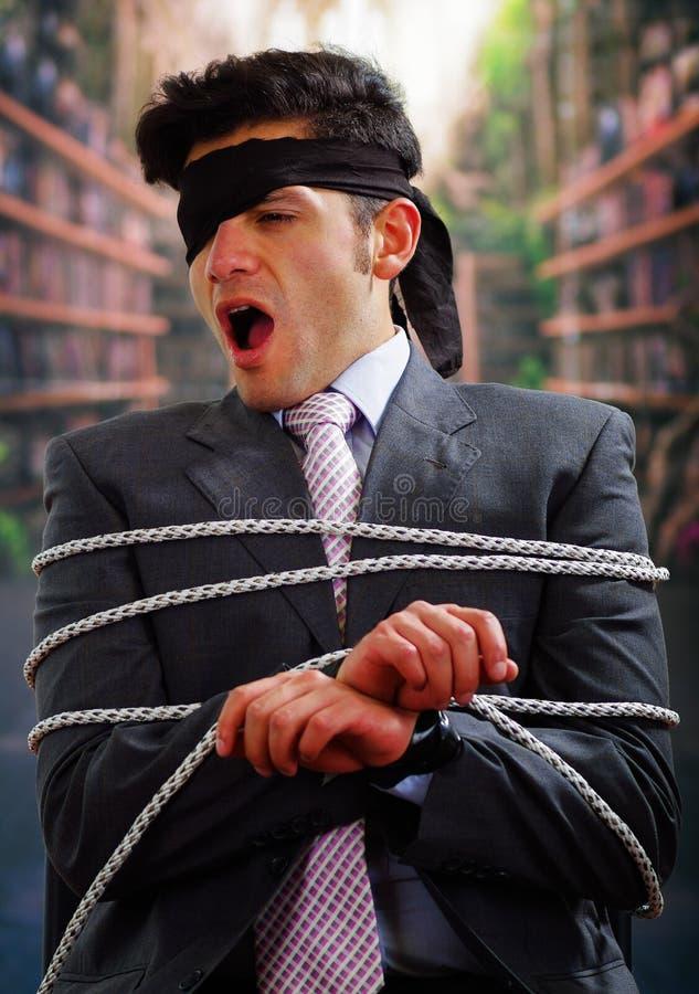 在与绳索的一把椅子困住的商人,与一块黑班丹纳花绸在他的头附近在被弄脏的背景中 免版税库存照片