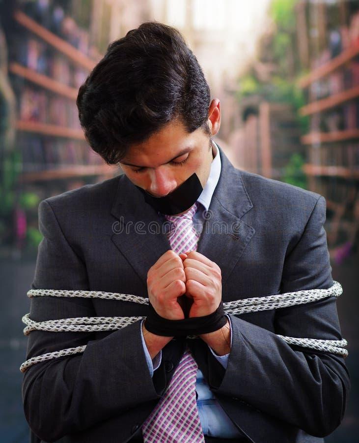 在与绳索的一把椅子困住的商人,与在他的嘴的一卷黑磁带和手在被弄脏的背景中 图库摄影