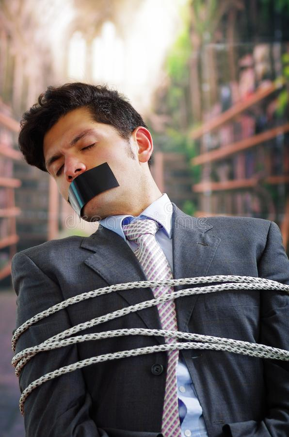 在与绳索的一把椅子困住的商人,与在他的嘴的一卷黑磁带和手在被弄脏的背景中 免版税库存图片