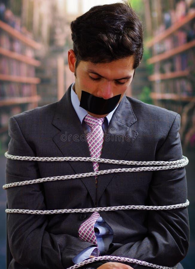 在与绳索的一把椅子困住的商人,与在他的嘴的一卷黑磁带在被弄脏的背景中 免版税图库摄影