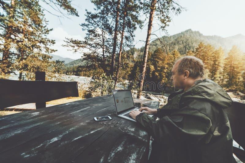 在与膝上型计算机和小配件outdoo的假期期间供以人员企业家 免版税库存照片