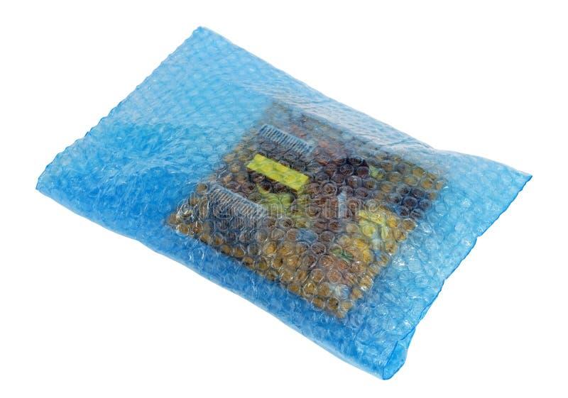 在与被隔绝的气泡的软的红色影片包装的备件和电子元件 库存照片