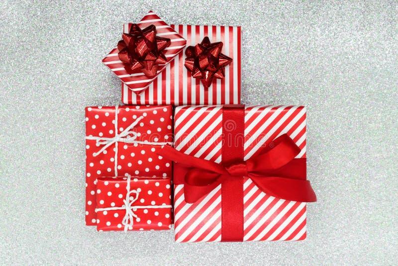 在与装饰品圣诞礼物箱子的红色纸包裹的各种各样的大小在发光的银色背景 免版税库存图片