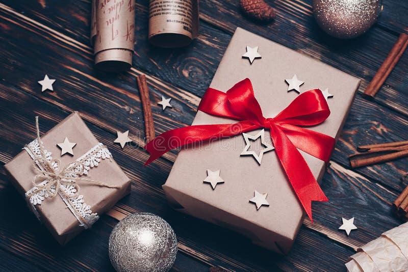 在与装饰的牛皮纸或当前箱子从上面包裹的圣诞节礼物在土气背景 平的位置样式 库存图片