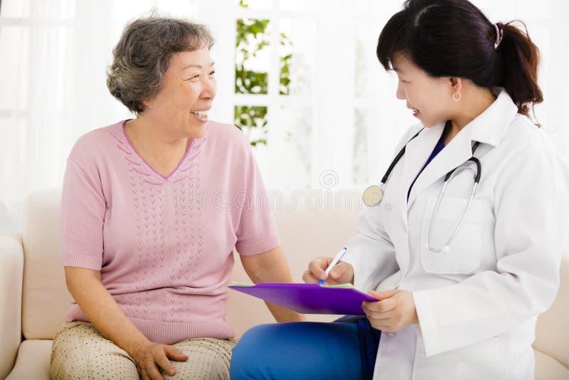 在与资深妇女的家庭参观期间护理做笔记 免版税库存照片