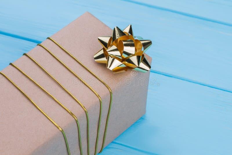 在与金黄丝带弓的工艺纸包裹的礼物盒 图库摄影