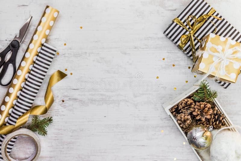 在与金黄丝带,条板箱的黑白有斑纹的纸充分包裹的礼物盒杉木锥体和圣诞节玩具和包裹m 免版税库存图片