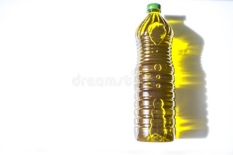 在与金黄反射的宠物装瓶的橄榄油 免版税库存图片