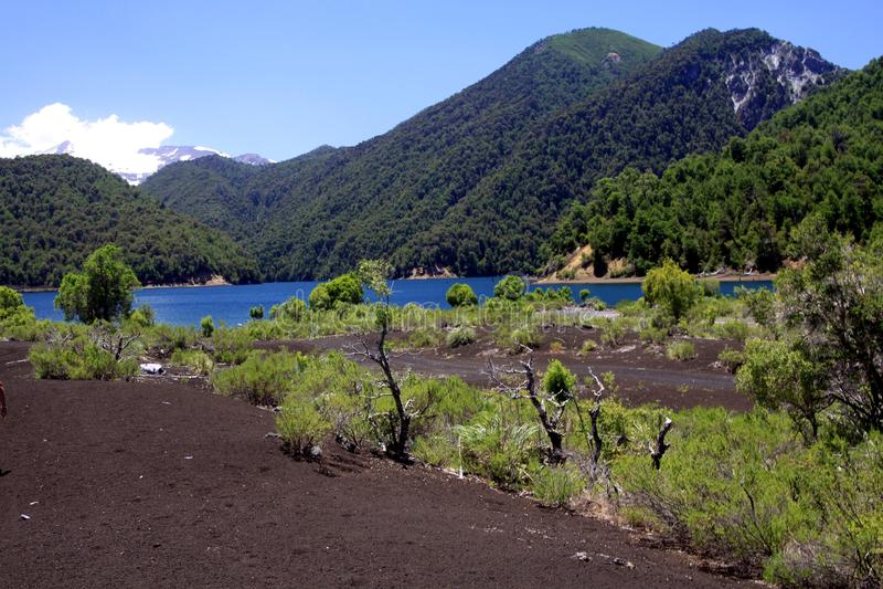 在与雪的山包围的深蓝色火山口湖的看法在Conguillio NP加盖了火山亚伊马火山在智利中部 免版税图库摄影