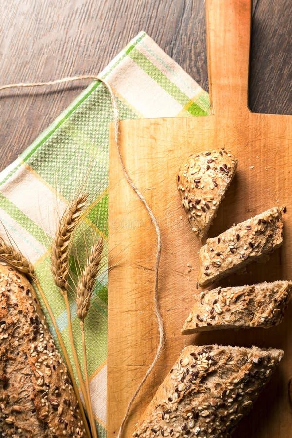 在与餐巾和麦子sp的一个木底部切的新鲜面包 库存照片