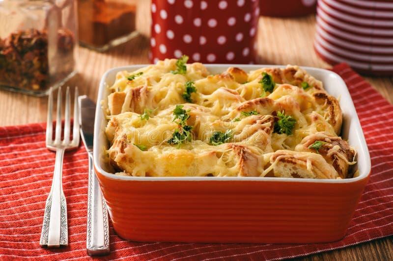 在与鸡、叫作地层和乳酪的砂锅上添面包的菠菜、鸡蛋 免版税库存照片