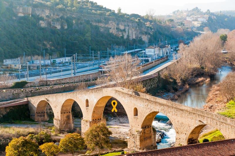 在与黄色的晴朗的冬日期间曼雷萨镇老桥梁看法,小加泰罗尼亚的镇的中世纪建筑学的标志, 库存图片