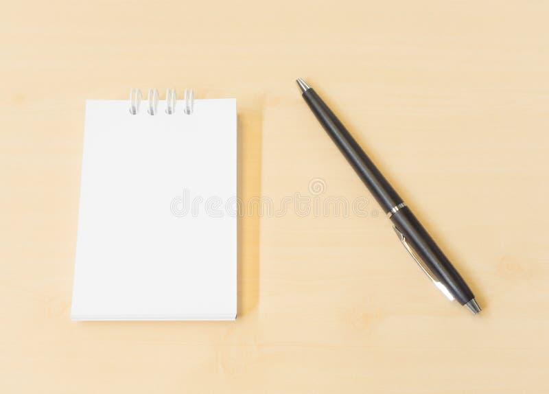 在与黑笔的木纹理背景安置的备忘录笔记 免版税库存照片