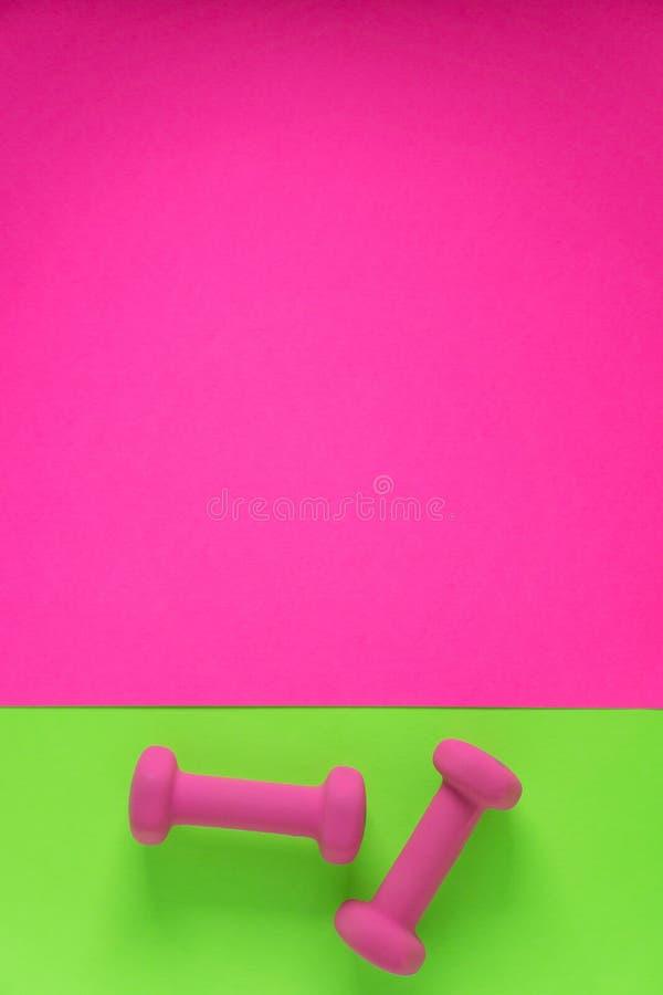 在与copyspace的柠檬绿和流行粉红背景有妇女的桃红色重量哑铃的健身设备隔绝的 免版税库存照片