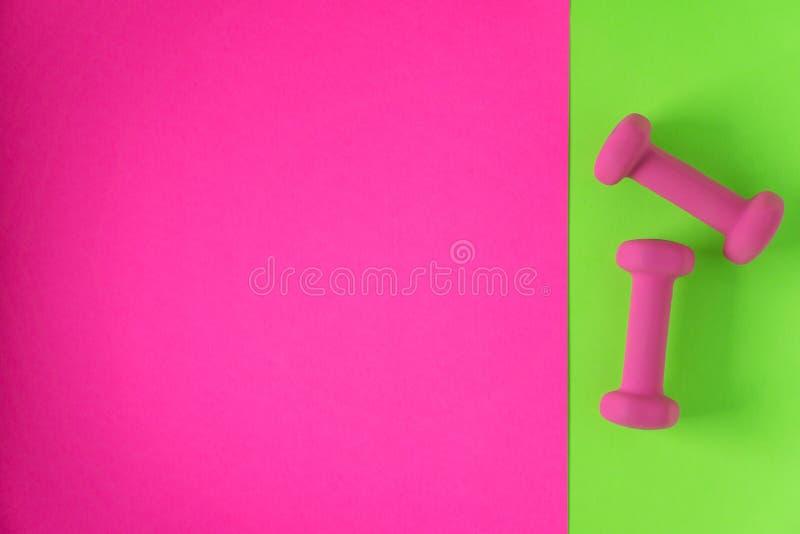 在与copyspace的柠檬绿和流行粉红背景有妇女的桃红色重量哑铃的健身设备隔绝的 免版税库存图片
