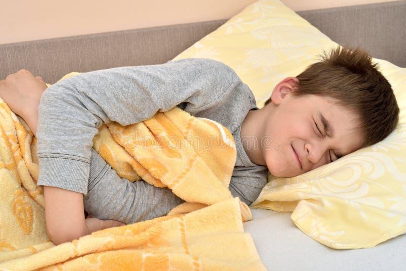 在与stomachache的床上的年轻男孩 库存图片