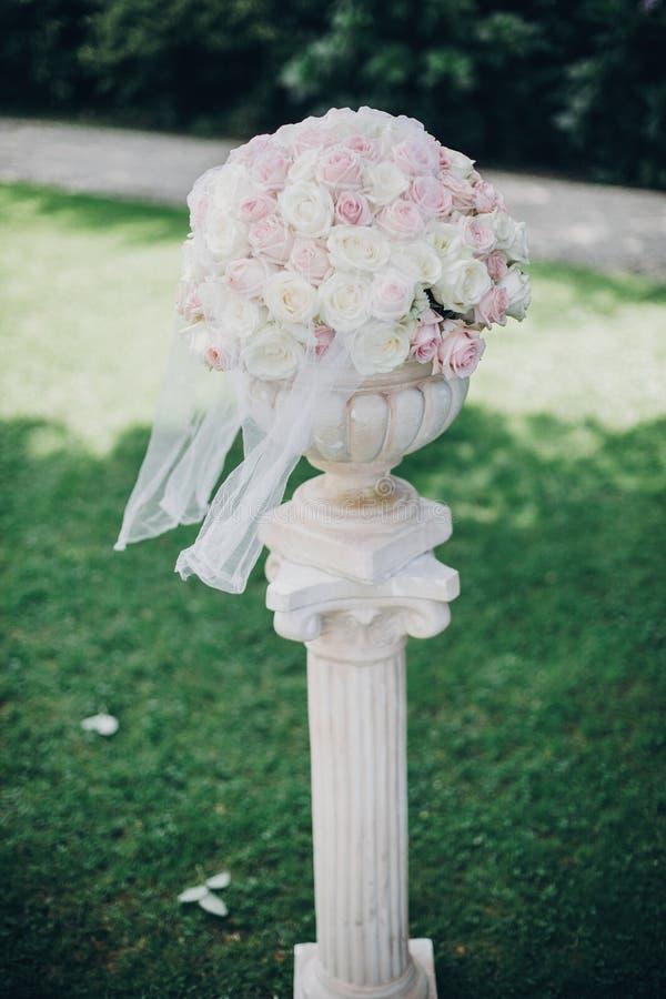 在专栏,婚姻的走道时髦的装饰的典雅的婚姻的花束户外 在结婚宴会的桃红色和白玫瑰安排 免版税库存图片