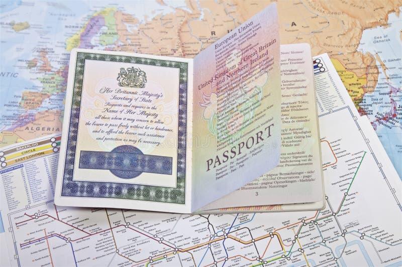 在世界地图的英国护照 库存图片