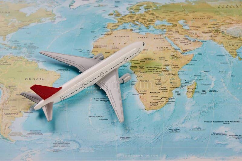在世界地图背景的白色玩具飞机 免版税库存图片