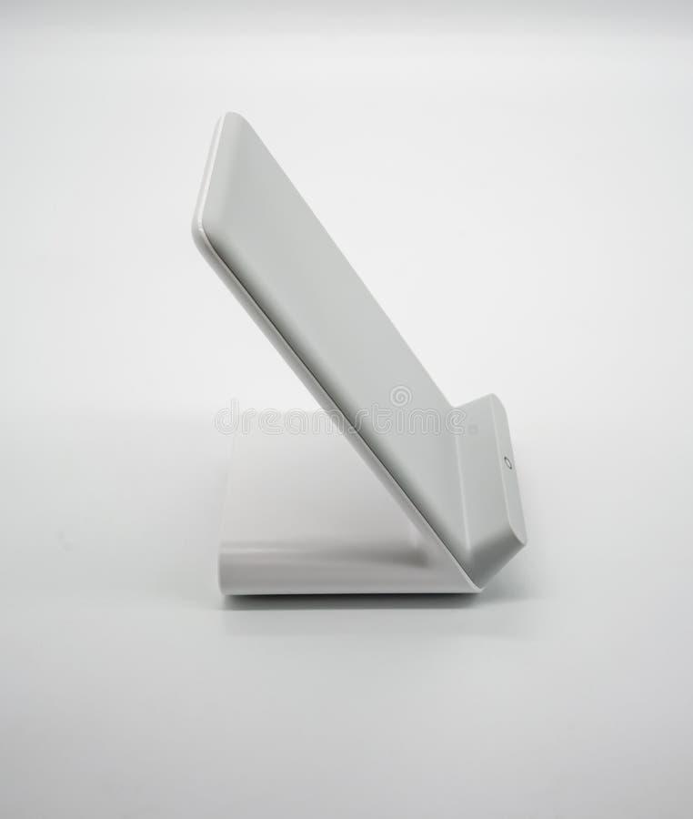 在丝毫与现代设计的白色无线充电器立场隔绝的 免版税库存图片
