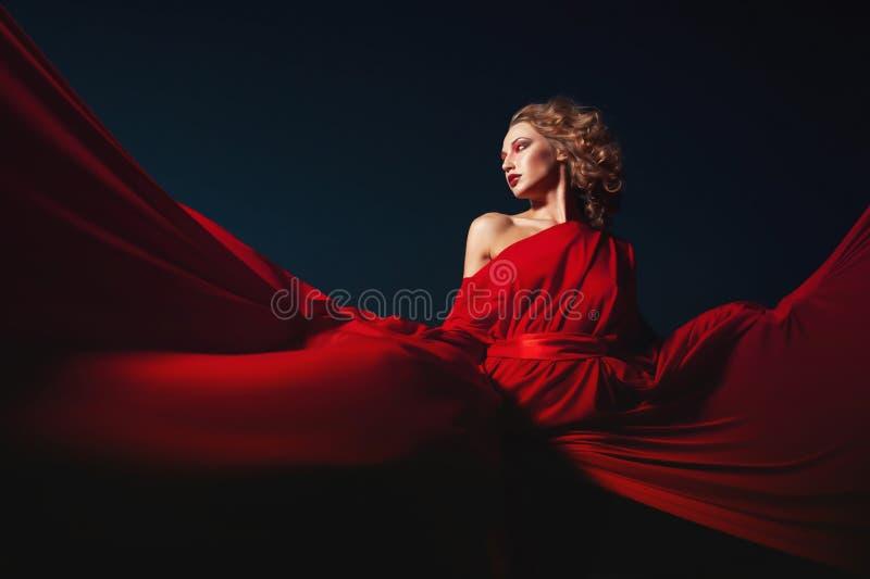 在丝绸礼服,艺术性的红色吹的褂子挥动的和飞来飞去的织品的妇女跳舞 免版税图库摄影