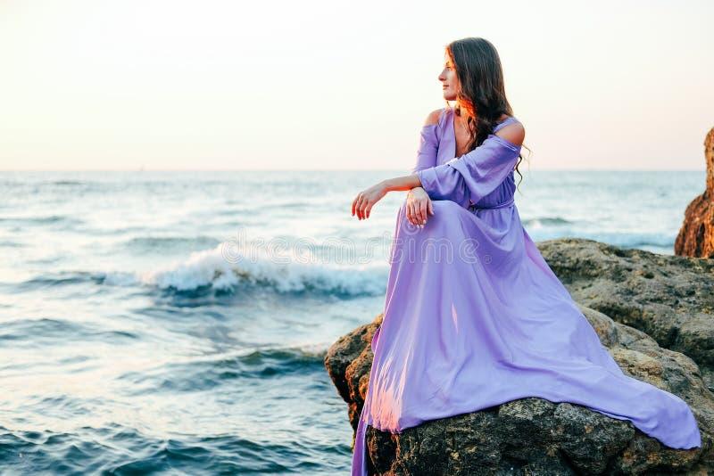 在丝绸紫色流动的礼服身分打扮的妇女在岩石 库存图片
