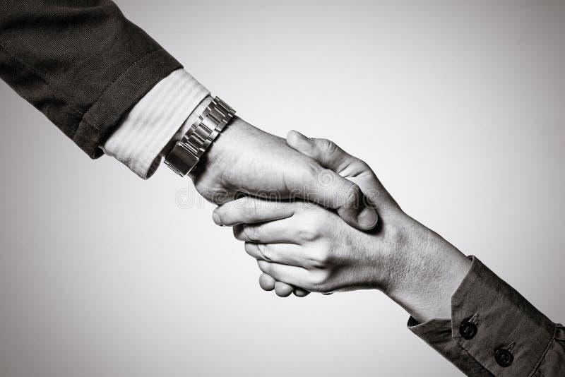 在两个伙伴之间的牢固的握手 免版税图库摄影