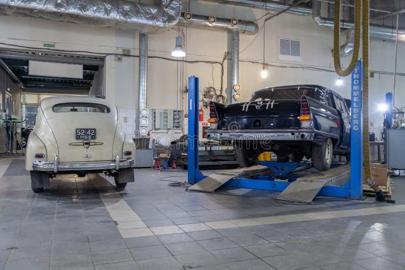 在两个俄国经典葡萄酒汽车gaz m20 pobeda的在维修车间身分状况良好一的背面图和13 chaika  免版税库存照片